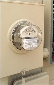 A photo of an electric meter contained in a beige metal box with the meter gauges displayed through a glass bowl-like covering.