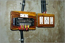 A photo of a charge controller. The charge controller—two rectangular-shaped boxes with switches and small, round indicator lights—has wiring running to and from it.