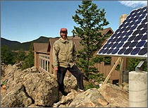 A photo of a man standing outside by a photovoltaic module installed on a rock outcropping with a house in background.